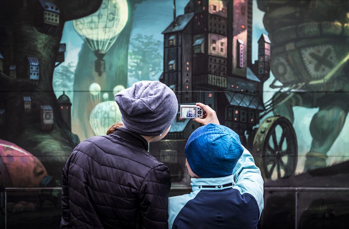 Barn fotograferar vägg med målning