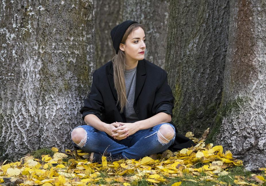 Kvinna sitter vid träd och höstlöv