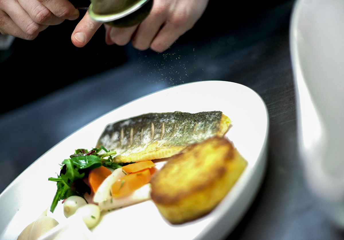 Maträtt med röding färdigställs i restaurangkök