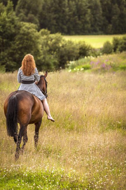 Kvinna rider ut på sommaräng med häst