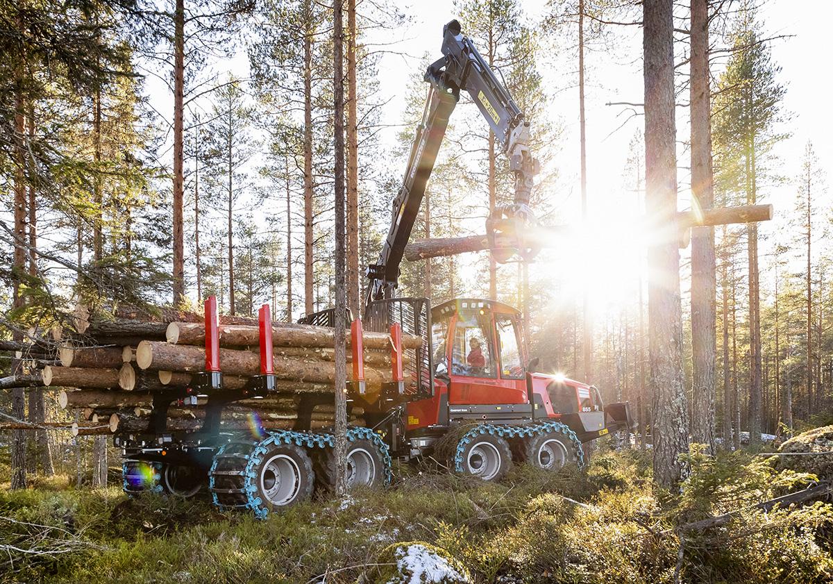 Skogsmaskin lyfter stock i skogen