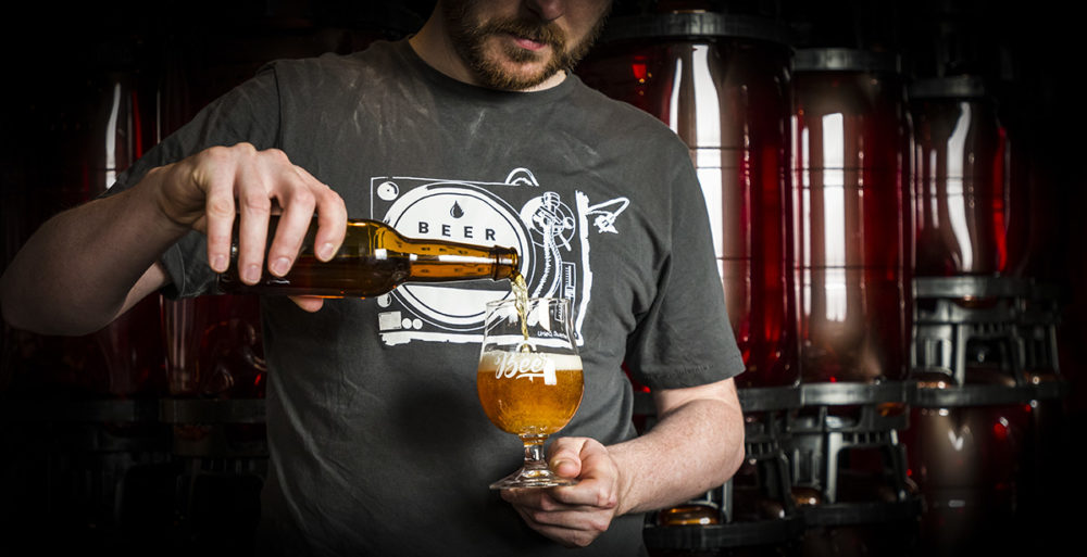 person häller upp öl i ölglas